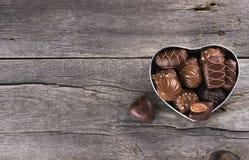 在一个箱子的巧克力以心脏的形式在黑暗的背景的 免版税库存图片