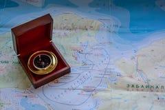 在一个箱子的指南针在地图 库存照片