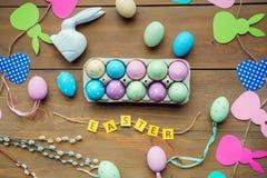 在一个箱子的色的鸡蛋在木背景的装饰围拢的中部 库存图片
