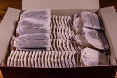在一个箱子的许多茶袋在木桌上 库存照片
