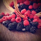 在一个篮子的不同的莓果在一张木桌上 免版税库存图片