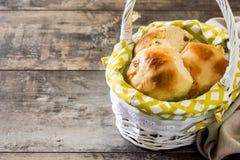 在一个篮子的传统复活节十字面包在木桌上