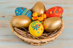 在一个篮子的复活节彩蛋与黄色婴孩鸡复活节概念 免版税库存照片