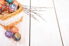 在一个篮子的复活节彩蛋在白色板条背景 图库摄影