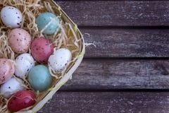 在一个篮子的多彩多姿的复活节彩蛋在一张棕色木桌上,与空间的复活节概念文本的 库存照片