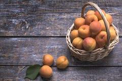 在一个篮子的成熟水多的杏子在木背景 顶视图 免版税库存照片
