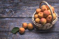 在一个篮子的成熟水多的杏子在木背景 库存图片
