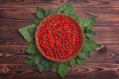 在一个篮子的成熟红浆果在木背景 水多的明亮的红色莓果 在一张黑褐色桌上的新鲜的雅致的无核小葡萄干 库存图片