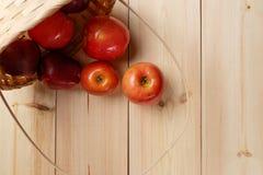 在一个篮子的成熟红色苹果在明亮的木背景 免版税库存图片