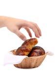 在一个篮子的新月形面包用手。 免版税库存照片