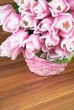 在一个篮子的桃红色郁金香在破旧的木背景 免版税库存照片