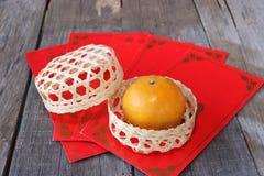 在一个篮子的桔子在有朱红色的信封小包或ang pao背景的老木板 愉快的春节概念 免版税图库摄影