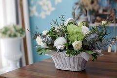 在一个篮子的美丽的花与绿色丝带 免版税库存照片