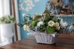 在一个篮子的美丽的花与绿色丝带 图库摄影