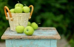 在一个篮子的自创土气绿色苹果在一把老凳子 图库摄影