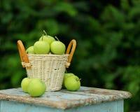 在一个篮子的自创土气绿色苹果在一把老凳子 库存照片
