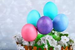 在一个篮子的色的复活节彩蛋在灰色具体背景 免版税库存图片