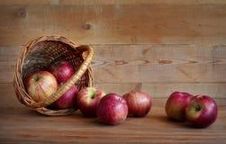 在一个篮子的苹果在木背景 免版税库存图片