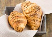 在一个篮子的酥脆新鲜的新月形面包在桌上 免版税库存照片