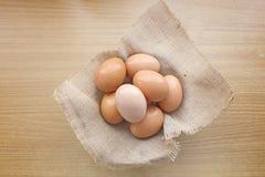 在一个篮子的鸡蛋在木桌背景 图库摄影