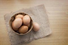在一个篮子的鸡蛋在木桌背景 免版税图库摄影