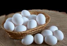 在一个篮子的鸡鸡蛋在木背景 免版税库存图片