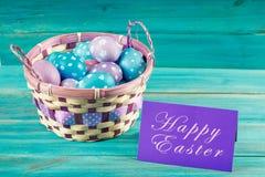 在一个篮子的紫罗兰色和蓝色复活节彩蛋与卡片 背景蓝色木 愉快的复活节 免版税库存照片