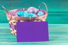 在一个篮子的紫罗兰色和蓝色复活节彩蛋与卡片 背景蓝色木 愉快的复活节 图库摄影