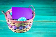 在一个篮子的紫罗兰色和蓝色复活节彩蛋与卡片 背景蓝色木 愉快的复活节 库存图片