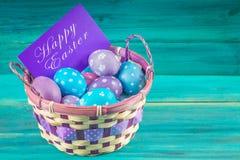 在一个篮子的紫罗兰色和蓝色复活节彩蛋与卡片 背景蓝色木 愉快的复活节 库存照片