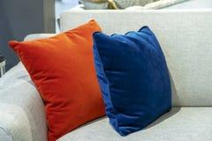 在一个米黄沙发的橙色和蓝色装饰枕头 免版税库存图片