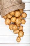 在一个粗麻布袋的嫩土豆土豆在白色木背景 免版税库存图片