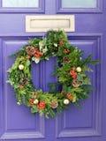 在一个紫色门的五颜六色的花圈 免版税图库摄影