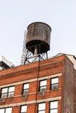 在一个红砖大厦上面的水塔 免版税库存照片
