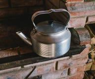 在一个红砖火炉的一个金属水壶 图库摄影