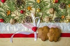 在一个红色丝带和鞋带边缘、巧克力金钟柏心脏与弓和小树枝的饼干  库存照片