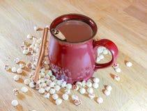 在一个红色假日杯子的热巧克力用肉桂条和whi 免版税库存照片
