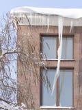 在一个红色大厦的大冰柱 免版税库存图片