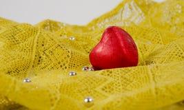 在一个红色套的巧克力心脏在黄色鞋带和银色小珠背景  库存照片