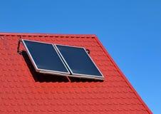 在一个红色屋顶的太阳电池板 免版税库存图片