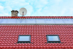 在一个红色屋顶的平的太阳能集热器 免版税库存图片