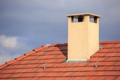 在一个红色屋顶顶部的烟囱 图库摄影