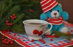 在一个红色帽子的一个小玩具玩具熊,云杉的分支用红色莓果和在它旁边的白色杯子在老木背景 免版税库存图片