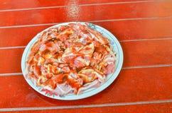在一个红色木地板上的一个盘用卤汁泡的猪肉 免版税库存照片