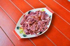 在一个红色木地板上的一块板材用卤汁泡的猪肉的机器 免版税库存照片