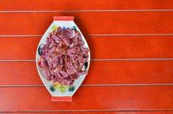 在一个红色木地板上的一块板材用卤汁泡的猪肉的机器 库存照片