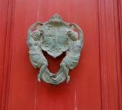 在一个红色木门的古色古香的敲门人 免版税库存图片