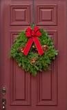在一个红色木门的圣诞节花圈 图库摄影