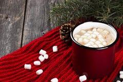 在一个红色杯子的圣诞节饮料热巧克力在一木backgroun 库存照片
