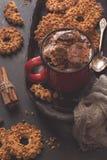 在一个红色杯子的热巧克力,与坚果的曲奇饼 舒适大气,被定调子的照片 选择聚焦 免版税库存照片